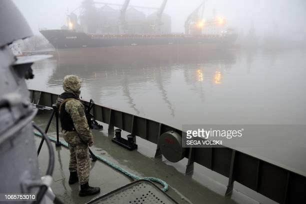Ukrainian soldier stands guard aboard military boat called Dondass moored in Mariupol Sea of Azov port on November 27 2018 Three Ukrainian navy...
