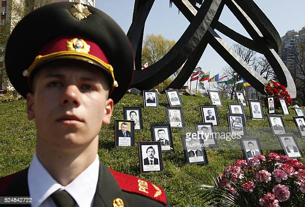 Ukrainian soldier stands guard near a monument honoring people who were killed during cleanup efforts after the Chernobyl nuclear power plant...