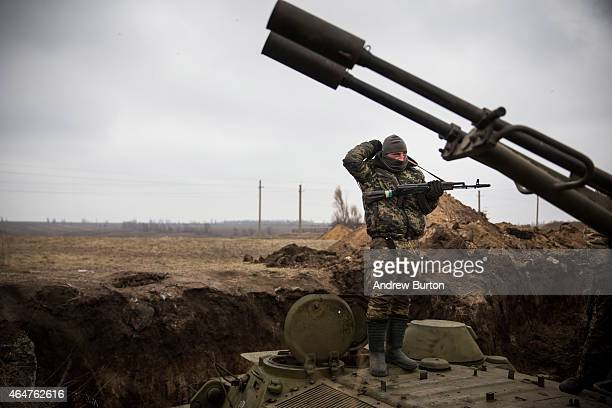 Ukrainian soldier stands on top of an armored personal carrier in a newly dug trench near the front line of defense against proRussian seperatists on...