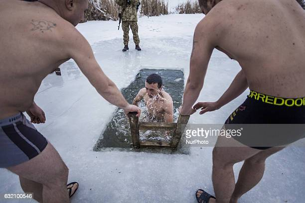 Ukrainian soldier with his colleagues inside frozen water during the traditional bath in the orthodox Epiphany in Memryk close to the Donetsk...