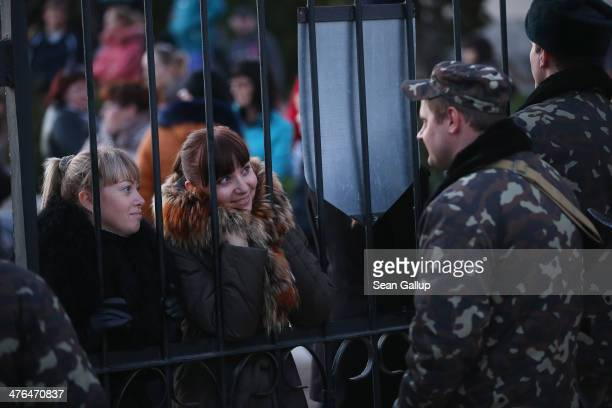 Ukrainian soldiers at the Belbek military base talk friends and family members through the gates of the base entrance on March 3, 2014 in Lubimovka,...