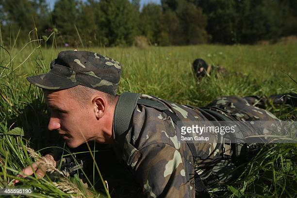 Ukrainian soldiers crouch in the grass before an ambush on a Lithuanian convoy on the third day of the 'Rapid Trident' bilateral military exercises...