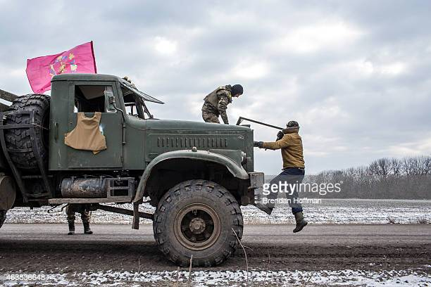 Ukrainian soldiers from a unit based in Zaporizhia repair the bulletshattered windshield of a truck after taking fire during their withdrawal from...