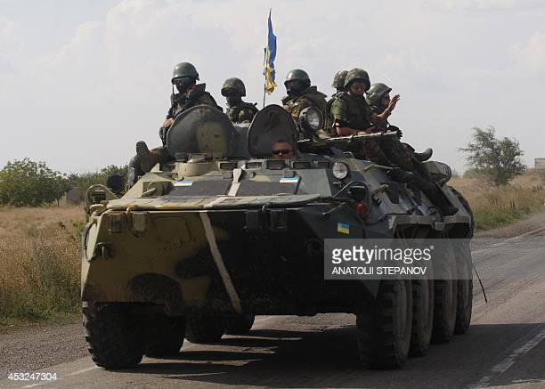 Ukrainian soldiers sit on a APC in the eastern region of Donetsk on August 6 2014 At least two civilians were killed as fighting erupted Tuesday...