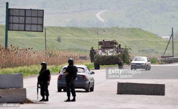 Ukrainian soldiers stand guard at a checkpoint on the road near the eastern city of Slavyansk Donetsk region on May 17 2014 Moscow today questioned...