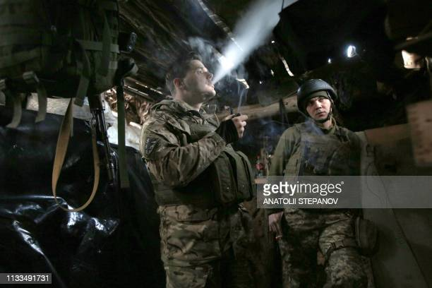 Ukrainian soldiers stand in a dugout on the front line, near Avdiivka, in Donetsk region on March 29 as a war with Russian-backed separatists in the...