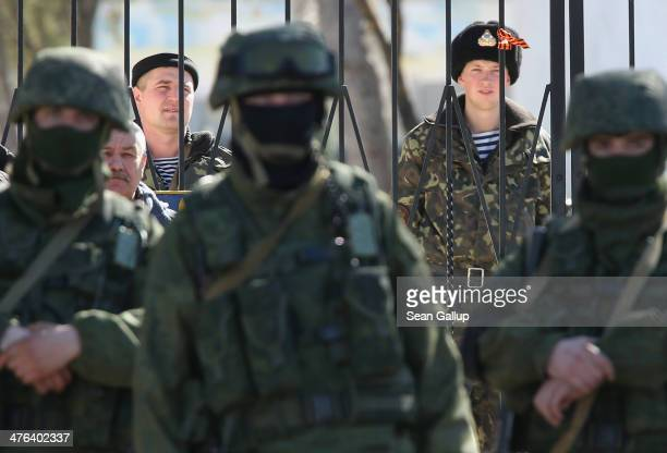 Ukrainian soldiers stand inside the gate of a Ukrainian military base as unidentified heavilyarmed soldiers stand outside in Crimea on March 3 2014...