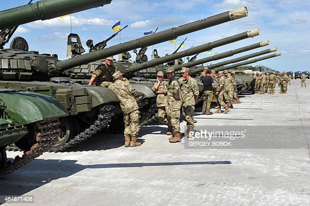 Ukrainian soldiers stand near tanks ahead of a ceremony marking the handing over of heavy military equipments to Ukrainian forces in northeastern...