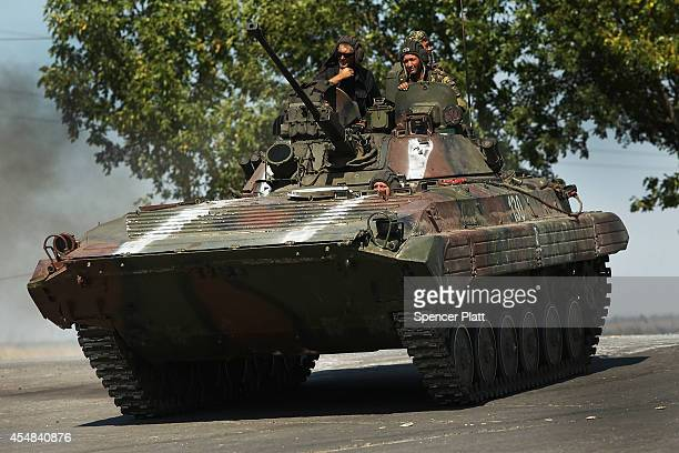 Ukrainian tank drives down a street on the outskirts of the strategic coastal city of Mariupol following an evening of heavy shelling by Russian...