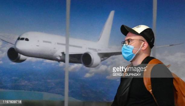 Ukrainian tourist walks in the arrival hall of the Internatioanal Boryspil airport outside Kiev after his plane landed from China on January 30,...