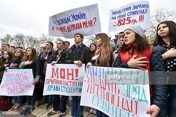 Ukrainian university students hold their hands over their hearts and placards reading 'We demand scholarship indexing' 'Hands off of student unions'...