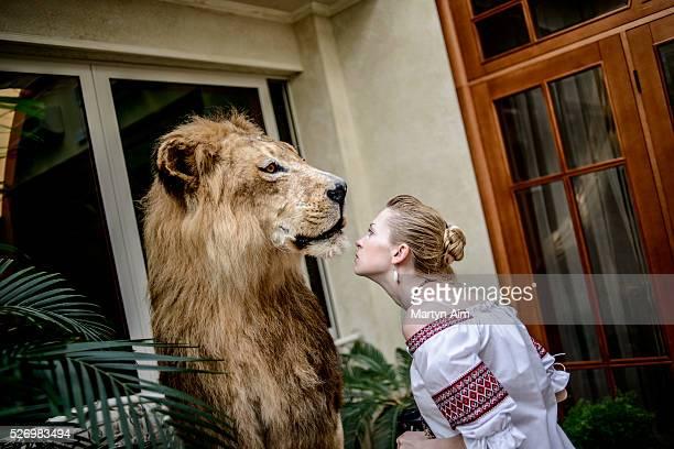 A Ukrainian woman in traditional dress inspects a taxidermy lion in the Kiev mansion of deposed Ukrainian president Viktor Yanukovych