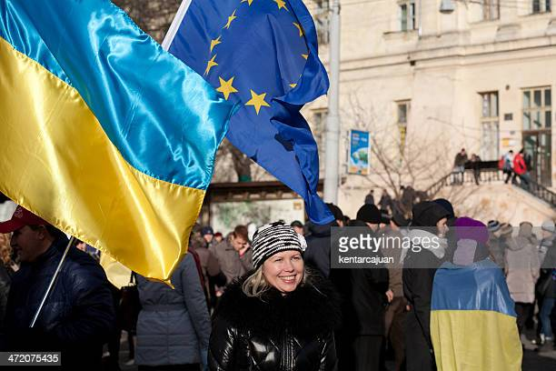 Ukrainian woman passing under EU and national flag