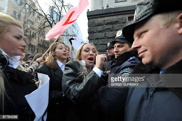 Ukrainian women's movement FEMEN activists try to force their way through a police cordon to reach the venue of the cabinet meeting during a protest...