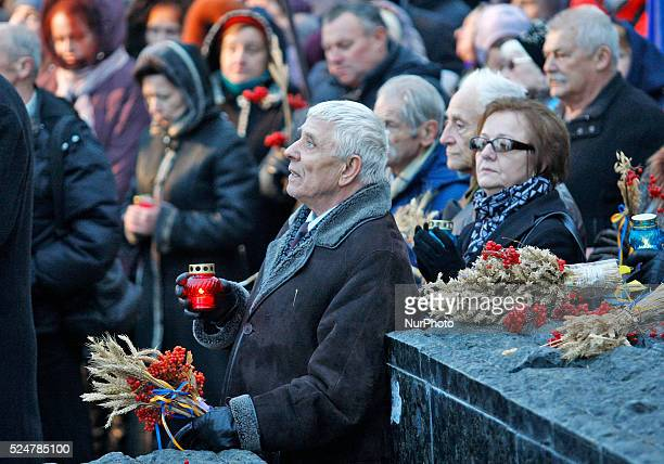 Ukrainians attend a memorial ceremony near a monument to the victims of the Great Famine in Kiev Ukraine28 November 2015 Ukrainians light candles to...