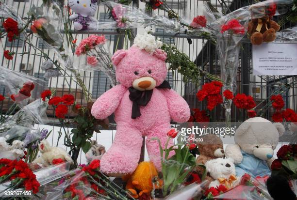 Ukrainians lay flowers and set candles and toys in tribute to the victims of a shopping mall fire in the Siberian city of Kemerovo outside the...