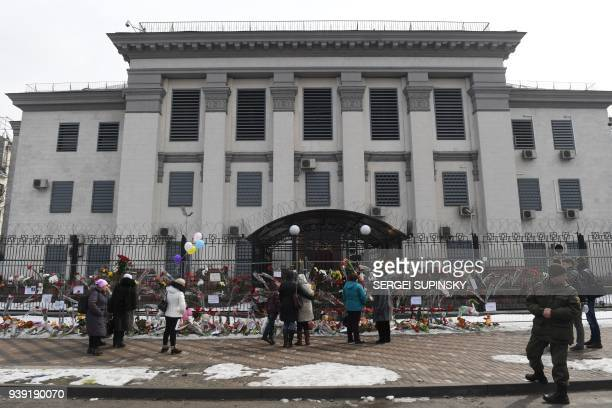 Ukrainians lay flowers set candles and toys outside the Russian Embassy in Kiev on March 28 in tribute to the victims of a shopping mall fire in the...