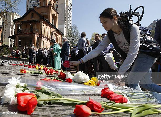 Ukrainians lay flowers to the monument of people who were killed during cleaning works after Chernobyl nuclear power plant disaster in Kiev Ukraine...