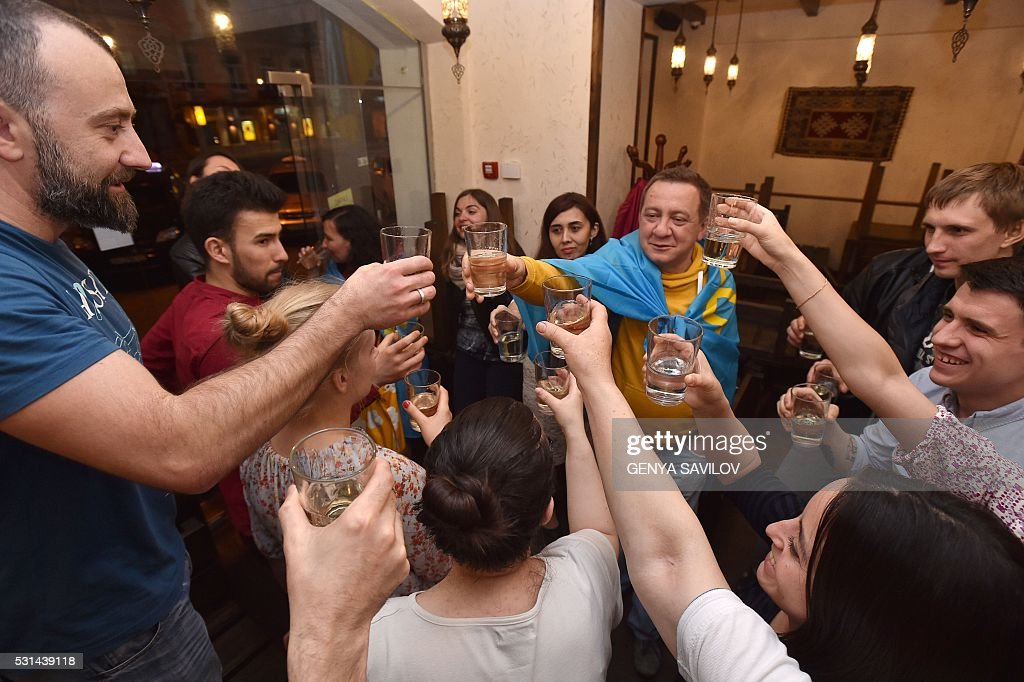 Ukrainians raise their glasses in cafe to celebrate the win of Jamala in the final of the Eurovision Song Contest 2016, in Kiev on May 15, 2016. krainian singer Jamala snatched victory from arch-rival Russia to win the Eurovision song contest, adding a touch of political drama to the annual kitsch extravaganza. / AFP / GENYA