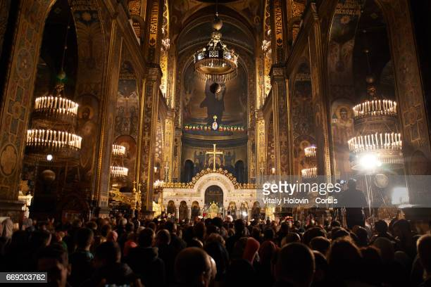 Ukrainians take part in an Orthodox Easter mass in which candles are lit from a Holy Flame taken from Church of the Holy Sepulcher in Jerusalem in St...