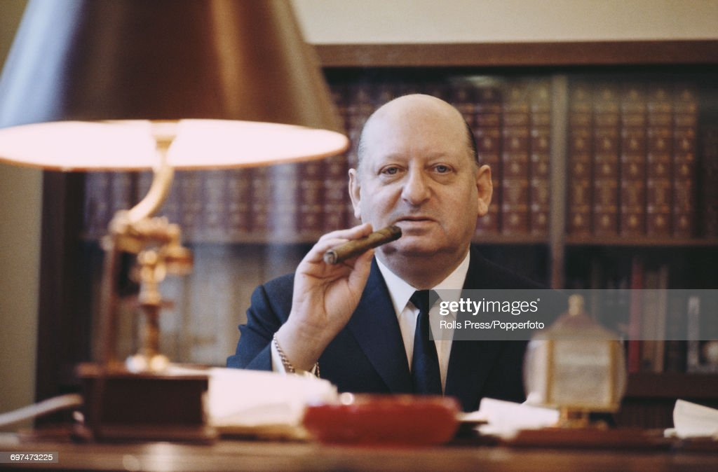 Ukranian born British television proprietor and media mogul, Sir Lew Grade (1906-1998) pictured smoking a cigar at his desk after being Knighted in the new year's honours list, London, January 1969.