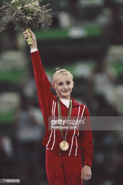 Ukranian gymnast Tatiana Gutsu of the Unified Team celebrates on the medal podium after receiving her gold medal after the Unified Team came first in...