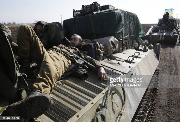 Ukranian servicemen rest on top of an Armoured Personnel Carriers ferrying cannons from their position near eastern Ukrainian city of Soledar in the...
