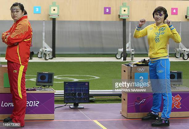 Ukrania's Olena Kostevych gestures next to gold medalist China's Guo Wenjun as she waits for the final results of women's 10m air pistol at the Royal...