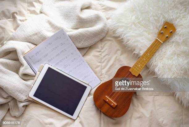 Ukulele and notebook of musical notes and a digital tablet on cozy blankets