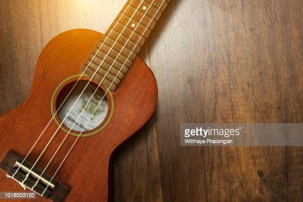 a ukulele on brown wooden background. - ukulele stock pictures, royalty-free photos & images