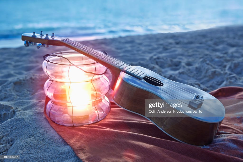 Ukulele resting on lantern on beach : Stock Photo