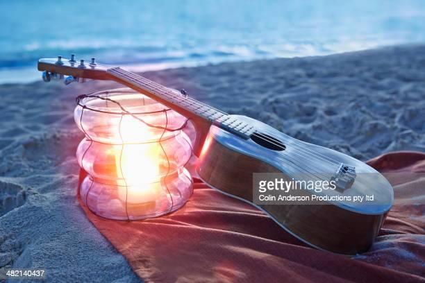 Ukulele resting on lantern on beach