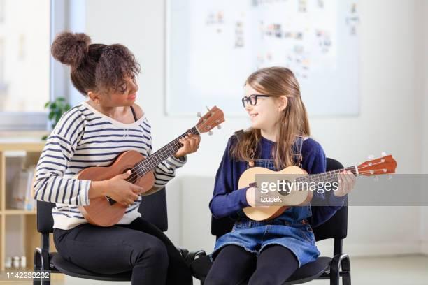 ukulele teacher with her student - ukulele stock pictures, royalty-free photos & images