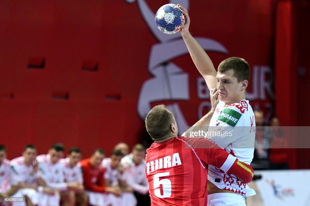 Uladzislau Kulesh (R) of Belarus vies for the ball with Vytautas Ziura of Austria during the preliminary round group B match of the Men's 2018 EHF European Handball Championship between Belarus and Austria in Porec on January 12, 2018. /