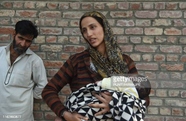 Ulfat an Indian Kashmiri mother holds her child as she waits outside a police station after her husband was detained during night raids in Srinagar...