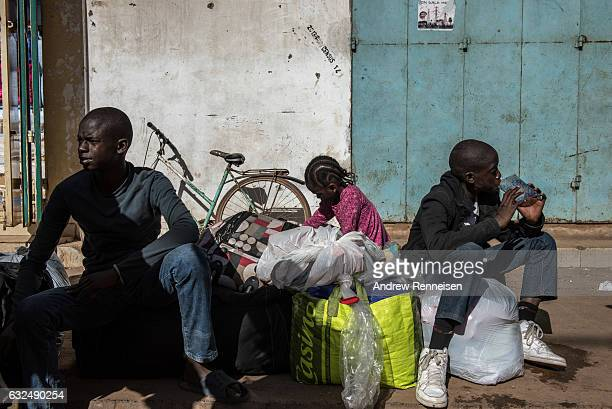Ulhaji Sesay his sister, Fatemahta and brother, Jibril wait for their mother outside the Banjul Ferry Terminal after returning home on January 23,...