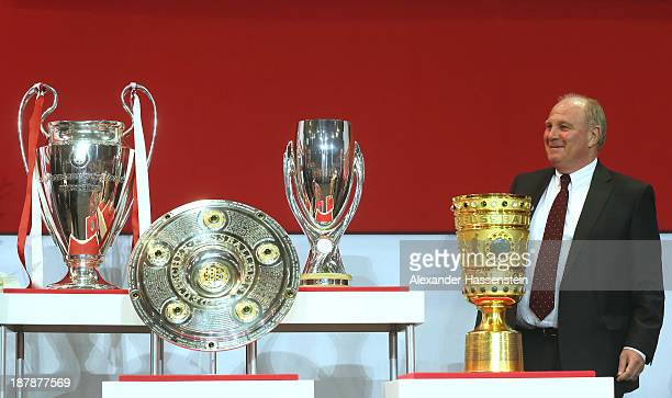 Uli Hoeness President of FC Bayern Muenchen poeses next to the UEFA Champions League winners trophy German League winners trophy the UEFA Super Cup...