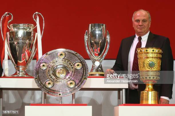 Uli Hoeness, President of FC Bayern Muenchen poeses next to the UEFA Champions League winners trophy , German League winners trophy , the UEFA Super...