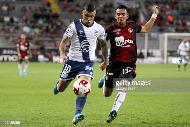 Ulises Cardona of Atlas battles for the ball with Christian Tabo of Puebla during their Mexican Clausura 2020 tournament football match at Jalisco...