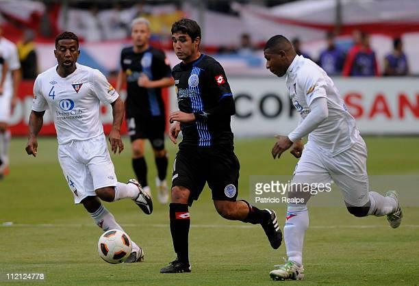Ulises de la Cruz and Jorge Guagua of Liga Deportiva Universitaria from Ecuador struggles for the ball with Alvaro Navarro of Godoy Cruz of Argentina...