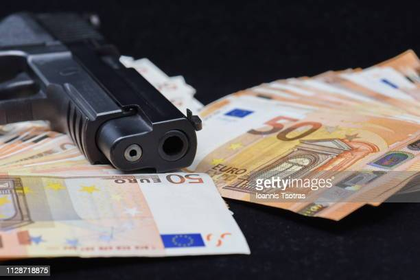 ull frame shot of fifty euro banknotes and a gun - 狙撃兵 ストックフォトと画像