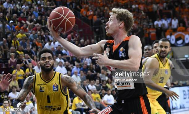 Ulm's Per Guenther and Ludwigsburg's DJ Kennedy vie for the ball during the German Bundesliga playoffs quarter final basketball match between MHP...