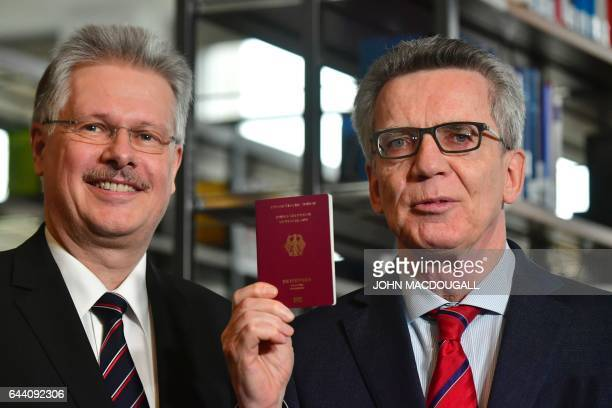 Ulrich Hamann Chief Executive Officer at Bundesdruckerei poses with German Interior Minister Thomas de Maiziere after handing him over the new...
