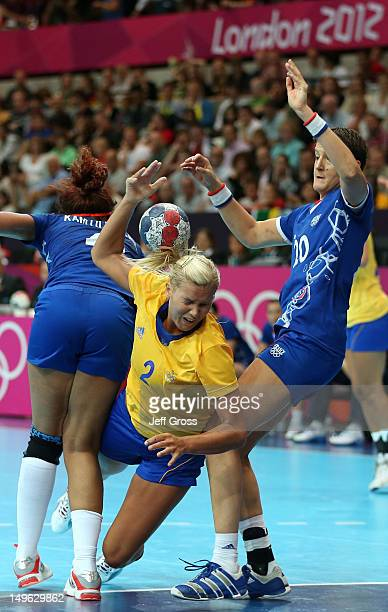 Ulrika Agren of Sweden is fouled in their Women's Handball Preliminaries Group B match against France on Day 5 of the London 2012 Olympic Games at...