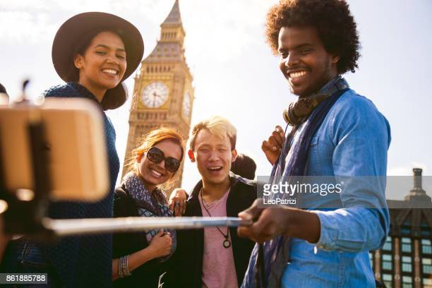 ulti ethnic group of friends taking a selfie with bigben in central london - central london stock pictures, royalty-free photos & images