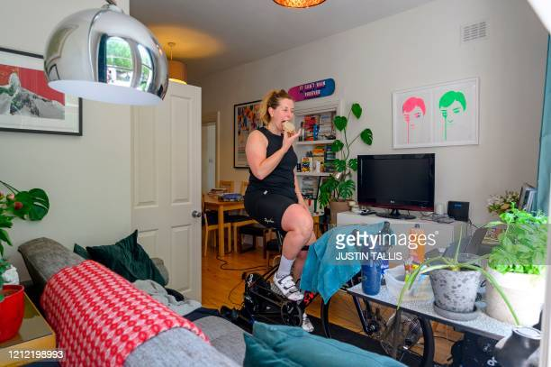 Ultra endurance cyclist Laura Scott eats a doughnut while cycling in the living room of her apartment on an indoor bike home trainer as she takes...