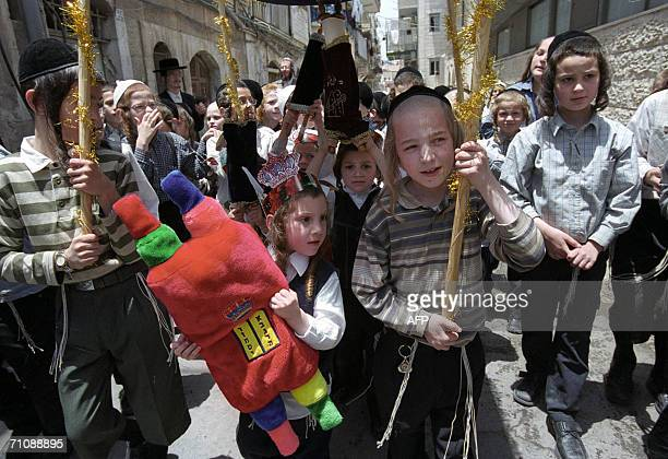 Ultra Orthodox children march with toy Torah scrolls at Mea Shearim neighborhood in Jerusalem 31 May 2006 during celebration of the Jewish holiday of...