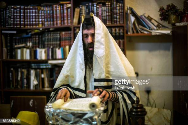 Ultra Orthodox family seen reading the book of Esther on March 13 2017 in Jerusalem Israel The carnivallike Purim holiday is celebrated with parades...
