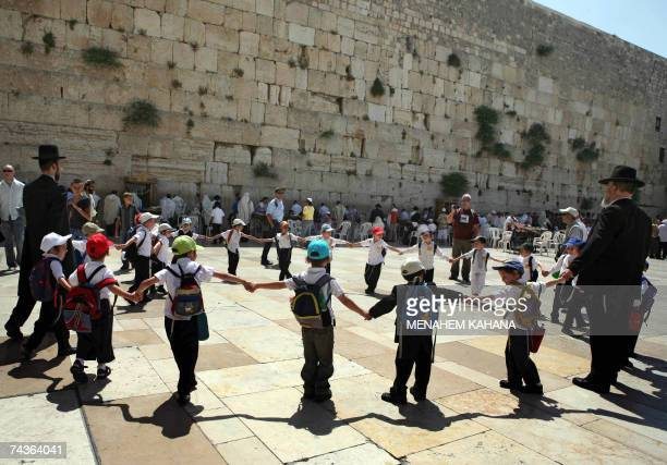 Ultra Orthodox Jewish boys hold hands to form a circle with their teachers at the Western Wall Judaism's most holy site as 13yearold boys participate...
