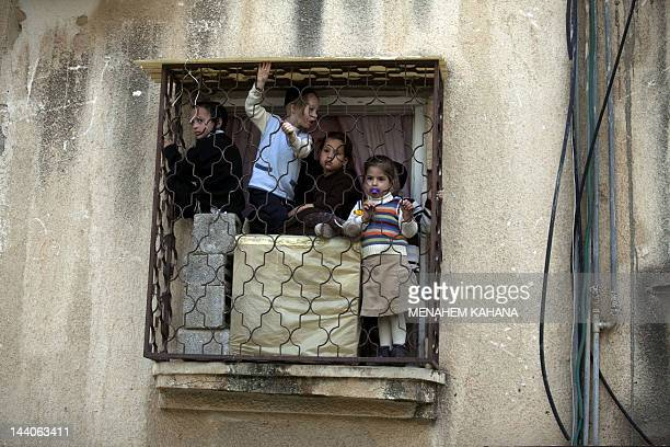 Ultra Orthodox Jewish children from the Vizhnitz Hasidic dynasty look from the window of their house the the funeral procession of their rabbi Moshe...